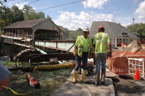 Workers for FairPoint stand by the road washout by the Quechee covered bridge, where crews worked to restore telephone, sewer, and water lines across the Ottauquechee River Wednesday. VTD/Andrew Nemethy