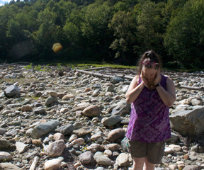 Rebecca Smith, overwhelmed by the sound of the White River and the memories it brings back, shields her ears among a field of rocks washed onto her property by the river during Tropical Storm Irene. VTD Photo/Taylor Dobbs