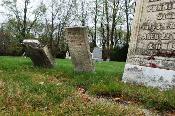 Gravestones lean in the soft delta sand at Merrill Cemetery in Colchester. Photo by Audrey Clark/for VTDigger