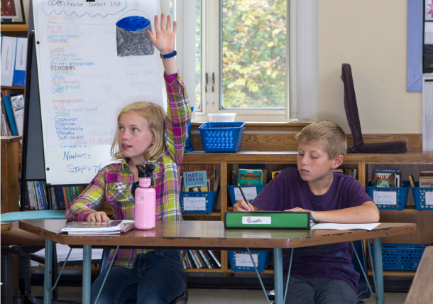 Union Elementary School fifth grade student Alex raises her hand to ask a question while classmate Brian edits his report. Students are in Windy Kelley's classroom the Montpelier school. Photo by Roger Crowley/for VTDigger