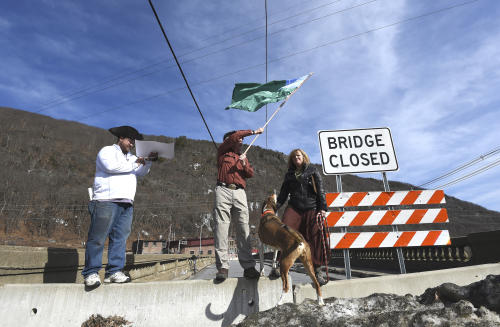 Emily Peyton (right), Mike Smith and Torin Brooks (left) stand on a barricade before reciting a declaration claiming the Vilas Bridge for the state of Vermont on Tuesday afternoon. Photo by Kayla Rice/BrattleboroReformer