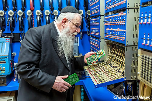 Rabbi Halberstam shows some of the custom-built computer hardware installed in the early 1990s. (Photo: Eliyahu Yosef Parypa/Chabad.org)