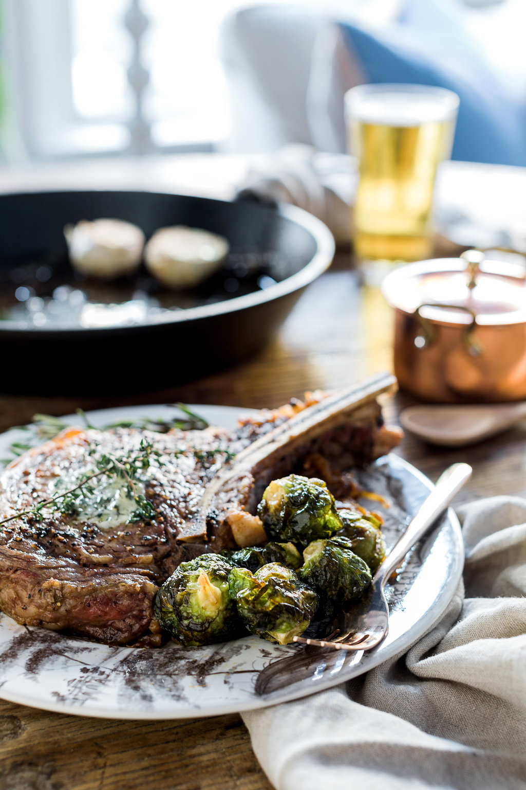 Skillet seared ribeye steak dinner with homemade herb butter, caramalized onions & fried brussel sprouts