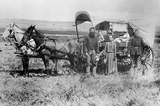 A family poses with the wagon in which they live and travel daily during their pursuit of a homestead, 1886.