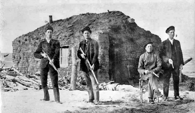 Homesteaders at Strool, South Dakota, 1909. Four men in front of a sod house, each holding a rifle or gun.