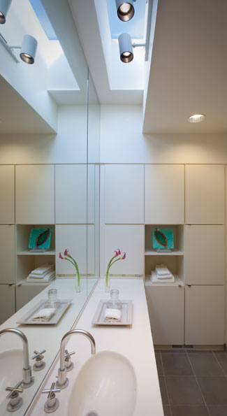 The bathroom with its oval sinks and ceiling windows reflect the unabashedly modern interiors of the home.