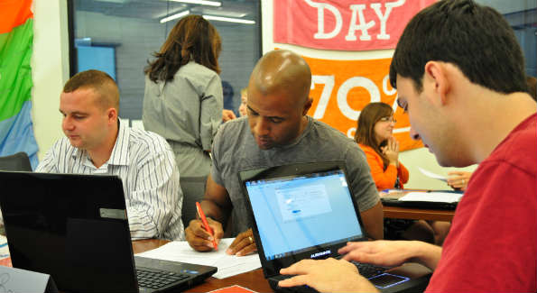 Mentor Bryan Bonner edits resumes with foster youth interns at Living Social Headquarters.