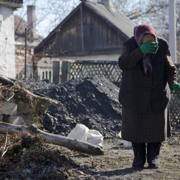PHOTO TAKEN OCT. 28, 2014 In this photo taken on Tuesday, Oct. 28, 2014, Lyubov Stasovskaya, 86 wipes tears in the backyard of her house in the town of Donetsk, eastern Ukraine.  Donetsk, which has lost about 400,000 of its 1 million pre-war population, is bracing to a winter ahead. In a climate like eastern Ukraine?s, where temperatures typically stay below zero all winter, the damage to the critical infrastructure and lack of effort to provide adequate shelter to people whose homes were destroyed could literally mean a death from the cold. (AP Photo/Dmitry Lovetsky)