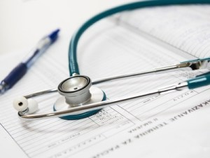 Healthcare - A stethoscope resting on a register book