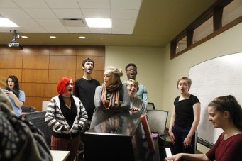 The cast of the LGBTQ Alliance's Rocky Horror Picture Show practices songs with musical director Gabi Anderson (right) in the East Academic Building. (Photo by Miranda Kenny)