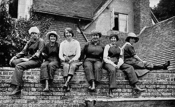"THE WAR BROWNIES RESTING DURING LUNCH TIME: MUNITION WORKERS OF ENGLAND. This sturdy, smiling sextet is a group typical of thousands of human ""cogs"" in Great Britain's vast machine which is supplying ammunition for the Empire's armies in France, in the Balkans, and in Mesopotamia, and which is also furnishing shells for the Russians and Italians."