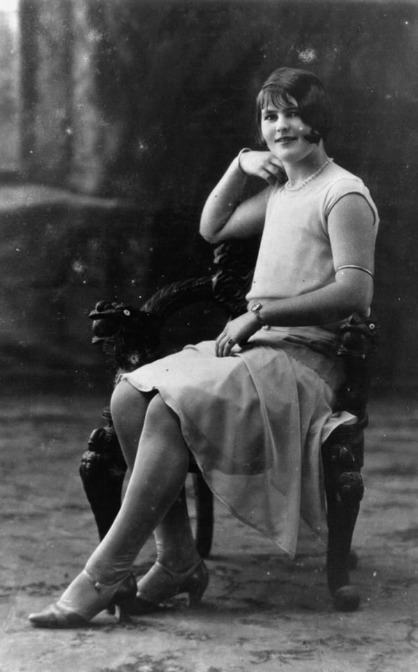 Miss Katie Fitzgerald. Stylish, studio photograph of a young woman in flapper attire. Miss Fitzgerald is sitting on an ornately carved armchair. c1920