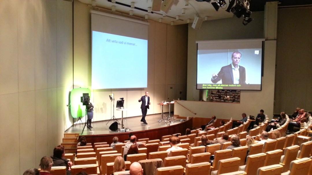 Bild på scen i Norra Latin med teckenspråkstolkar och textad video på storbildsskärm