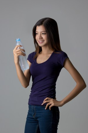 Young Asian woman with drinking water on isolated background