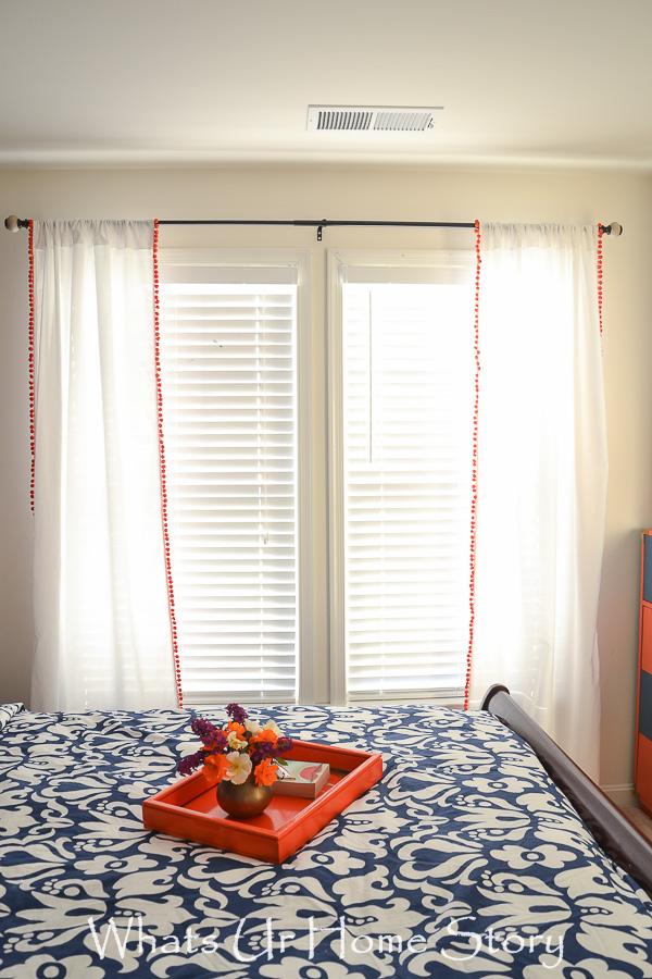 Cut a full sheet in half, hem the end, add pom pom fringe =Awesome curtains