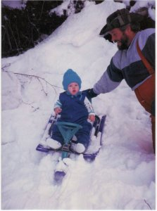 Nate's dad pushing little Nate on a  sled.