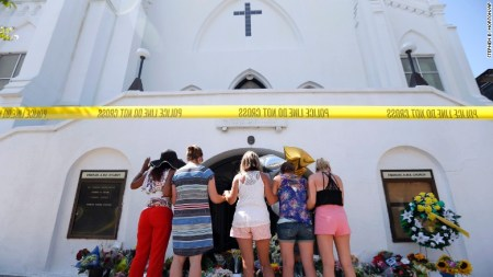 A group of women pray together at a makeshift memorial on the sidewalk in front of the Emanuel AME Church on June 18.