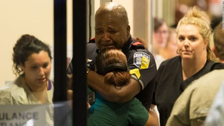 A Dallas Area Rapid Transit (DART) police officer receives comfort at Baylor University Hospital emergency room entrance on July 7 in Dallas, Texas. Shooters killed five officers during protests against police in downtown Dallas, marking the deadliest single attack on law enforcement since September 11, 2001.