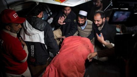 Pakistani rescue workers and volunteers transport caskets carrying bodies of the plane crash victims