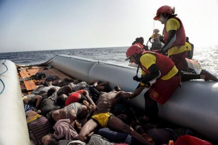 Members of Spanish humanitarian NGO Proactiva Open Arms, drag corpses of refugees and migrants after a rescue operation off the coast of Libya on October 4, 2016 (AFP Photo/ARIS MESSINIS)