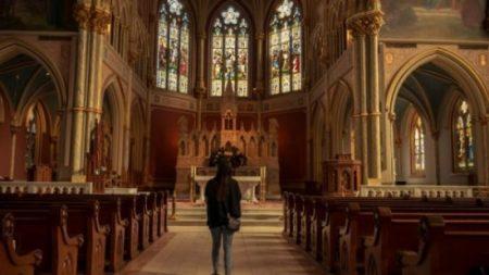 A woman stands inside a church.