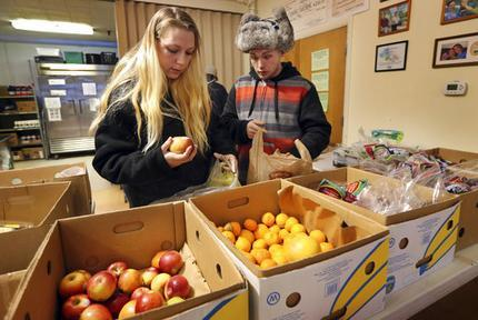 In this Monday, March 27, 2017 photo Sunny Larson, left, and Zak McCutcheon pick produce while gathering provisions to take home at the Augusta Food Bank in Augusta, Maine. Republican Gov. Paul LePage says his call to ban the use of food stamps for soda and candy is backed by science and a desire to reduce obesity and diabetes in the nation's oldest state. (AP Photo/Robert F. Bukaty)