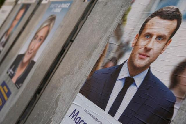 People walk past campaign posters of Emmanuel Macron (L), head of the political movement En Marche! (Onwards!), and Marine Le Pen (R), French National Front (FN) political party leader, two of the eleven candidates who run in the 2017 French presidential election, are seen in Paris, France, April 10, 2017. (REUTERS/Gonzalo Fuentes)