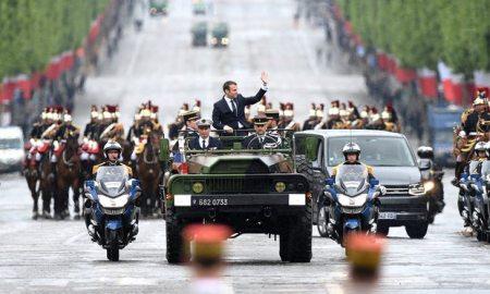 Macron waves from a military vehicle. Photograph: Abd Rabbo Ammar/EPA