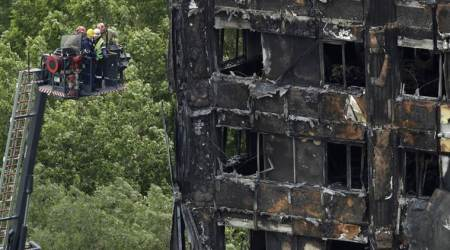 Emergency workers on a raised platform point at a section of the fire-gutted Grenfell Tower in London, Friday, June 16, 2017, after a fire engulfed the 24-story building Wednesday morning. London firefighters combed through the burned-out public housing tower Thursday in a grim search for missing people as police and the prime minister launched investigations into the deadly inferno, with pressure building on officials to explain the disaster and assure that similar buildings around the country are safe. (AP Photo/Matt Dunham)