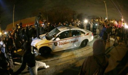 A protester squirts lighter fluid on a police car as the car windows are shuttered near the Ferguson Police Department after the announcement of the grand jury decision not to indict police officer Darren Wilson in the fatal shooting of Michael Brown.