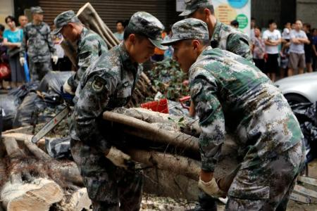 People's Liberation Army (PLA) soldiers clean branches of an uprooted tree after Typhoon Hato and Tropical storm Pakhar hit Macau, China August 27, 2017. REUTERS/Tyrone Siu