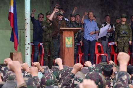 "Philippine President Rodrigo Duterte (on stage in brown) raises a clenched fist as he declares Marawi ""liberated"" during a ceremony in the Bangolo district of Marawi on Tuesday."