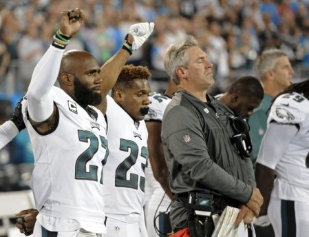 Philadelphia Eagles Malcolm Jenkins and Rodney McLeod raise their fists as they stand with Coach Doug Pederson during the national anthem on Oct. 12. (Mike Mccarn/Associated Press)