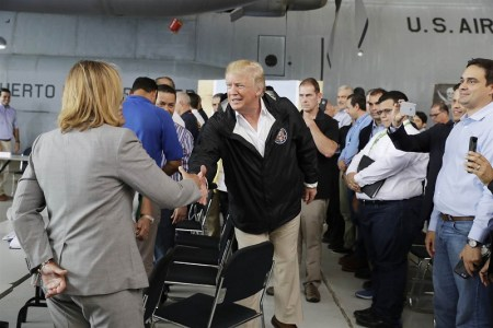 President Donald Trump arrives at Luis Muniz Air National Guard Base to survey hurricane damage and recovery efforts and shakes hands with the mayor of San Juan. (Evan Vucci / AP)