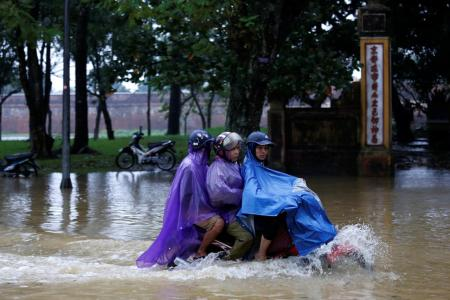 People ride a motorcycle along flooded road after typhoon Damrey hits Vietnam in Hue city, Vietnam November 5, 2017. REUTERS/Kham