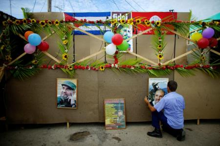 A man hangs pictures of late Cuban president Fidel Castro on a stage to be used during celebrations of what would have been his 91st birthday in San Antonio de los Banos, Cuba, August 10, 2017. Picture taken on August 10, 2017. REUTERS/Alexandre Meneghini