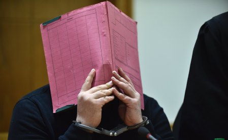 FILE - The Jan. 22, 2015 file photo shows former nurse Niels Hoegel covering his face during his trial at the regional court in in Oldenburg, northern Germany. The prosecutors in Oldenburg on Thursday, Nov. 9, 2017 said that he might have killed more than 100 people based on a toxicologic investigation. (Carmen Jaspersen/dpa via AP)