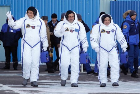 Russian cosmonaut Anton Shkaplerov, center, U.S. astronaut Scott Tingle, right, and Japanese astronaut Norishige Kanai, members of the main crew of the expedition to the International Space Station (ISS), walk to report to members of the State Committee prior the launch of Soyuz MS-07 space ship at the Russian leased Baikonur cosmodrome, Kazakhstan, Sunday, Dec. 17, 2017. (AP Photo/Dmitri Lovetsky, pool)