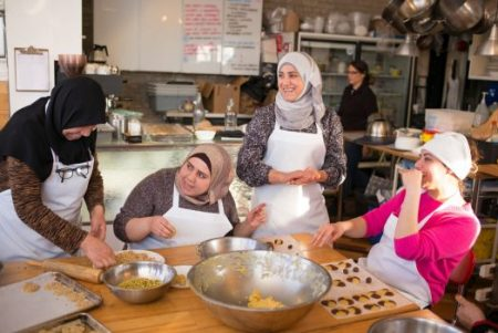 In the kitchen this month at Newcomer Kitchen, a project in Toronto that began in March 2016 as a way of giving newly arrived Syrian refugees who were temporarily living in airport hotels a chance to cook a meal. From left, Amina Alshaar, Aisha Mastou, Muna Nazha and Rahaf Alakbani. Ian Willms for The New York Times