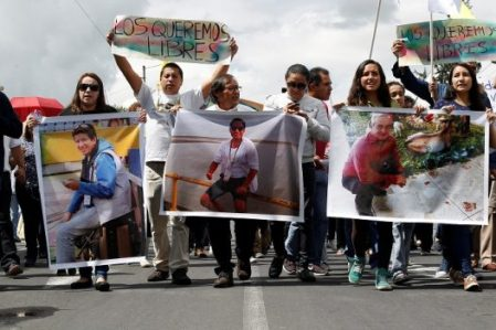 "Relatives and friends hold pictures of Ecuadorean photojournalist Paul Rivas (L), journalist Javier Ortega (C) and their driver Efrain Segarra, who were kidnapped near the Colombian border, during a protest march to demand for their release, in Quito, Ecuador April 1, 2018. The sign at the back reads: ""We want them free."" REUTERS/Daniel Tapia"