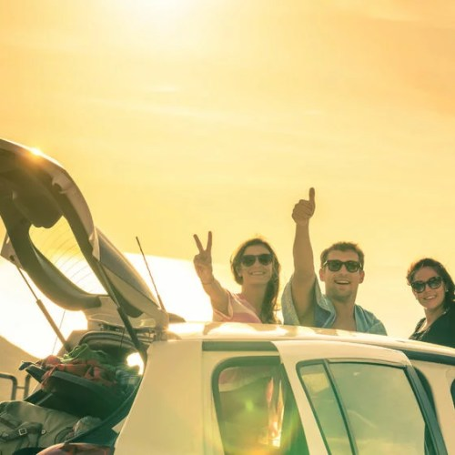 46167659 - best friends cheering by car road trip at sunset - group of happy people outdoor on vacation tour - friendship concept at travel with positive nostalgic emotions - soft focus due to backlight contrast