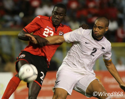 Photo: Nineteen year old Trinidad and Tobago striker Rundell Winchester (left) tussles with New Zealand captain and West Ham defender Winston Reid during their international friendly in Port of Spain in September 2013. (Courtesy Wired868)