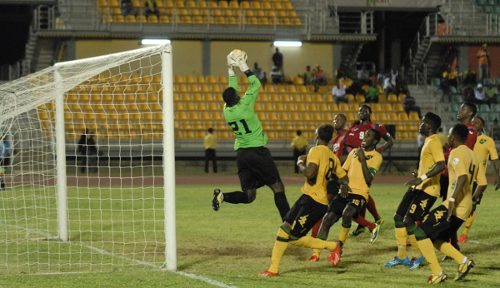 Photo: Trinidad and Tobago goalkeeper Jan-Michael Williams (left) hangs on to a cross while Jamaican opponents follow up in vain. (Courtesy TTFA Media)