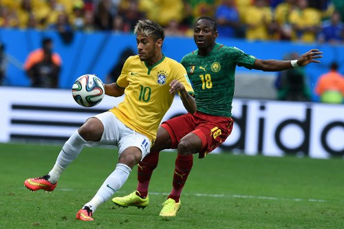Photo: Brazil forward Neymar (left) prepares to flick the ball around Cameroon midfielder Enoh Eyong.   (Copyright AFP 2014/Vanderlei Almeida)