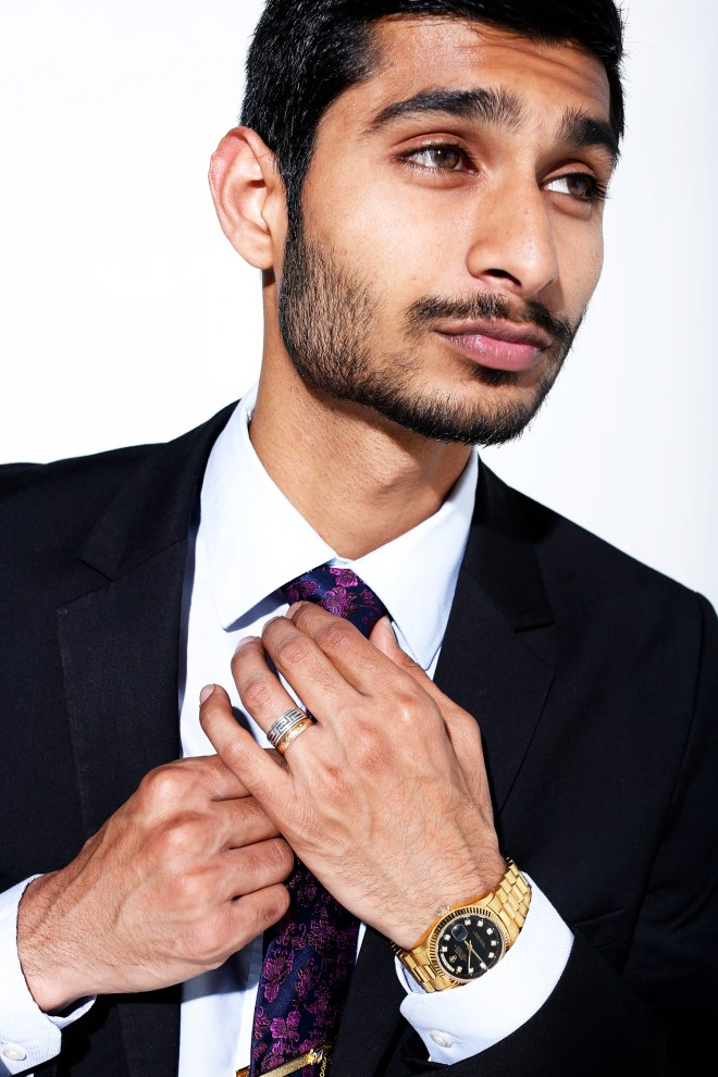 Rafey Wahlah models an Oyster Perpetual gold black faced Rolex Watch retailed at $12,550. The watch was a gift from his grandfather and matches the gold ring he wears from his grandmother that symbolizes eternal love.