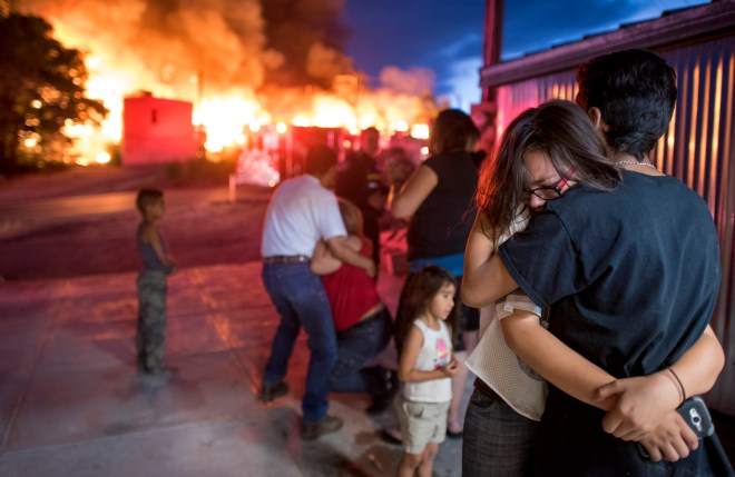 Inez Grace is held by her brother Leo Gomez as they watch their homes burn on Saturday June 26, 2016 in the Gamerco neighborhood on in Gallup, Nm.