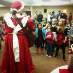 Mrs. Claus singing with the kids at a company Christmas party.