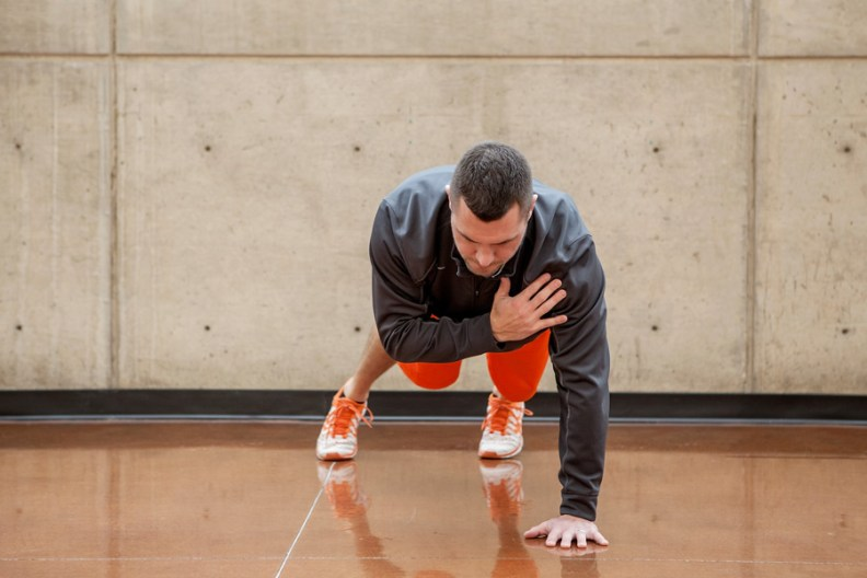 Chris Gillies positioning one hand on his chest, one hand on floor