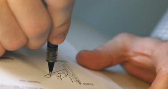 a close up image of a person signing a form