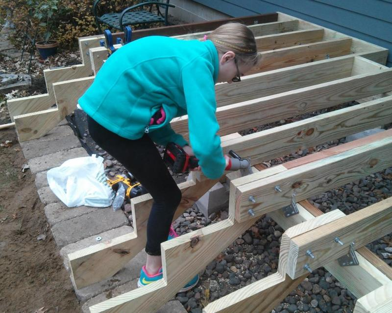 13 - My daughter bolting the stringers to the joists